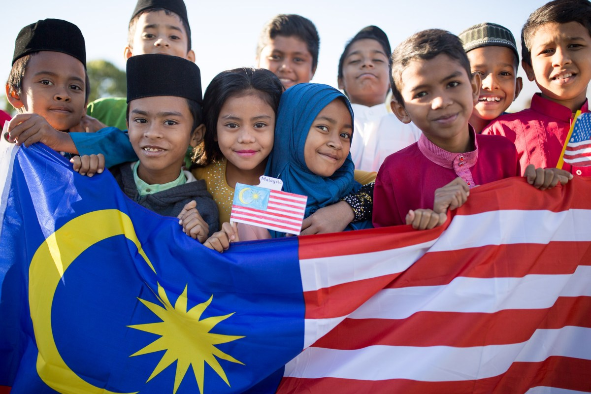 Children from Malaysia gather for a photograph behind their country's flag.