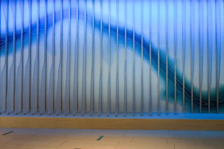 An illuminated wall inspired by the San Antonio River is prominently displayed in the main entrance.