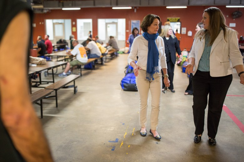 Patricia Barnes walks with Haven for Hope Director of Volunteer Services Melody Mcrea through the cafeteria that feeds over 1200 meals a day to the hungry.