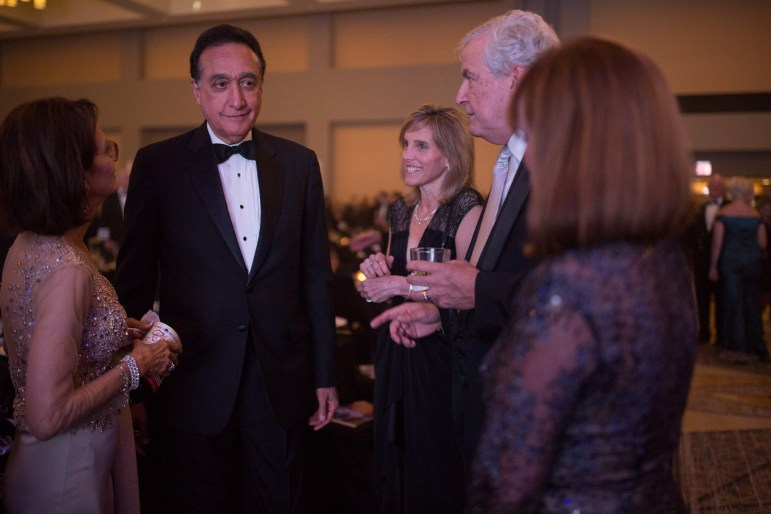 Henry Cisneros talks with guests in the ballroom just before the ceremony begins.