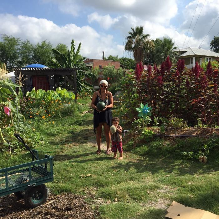 Lorie Solis with her and Skeets' son Phoenix reaping what theyve sown: corn, amaranth, basil, and melons.