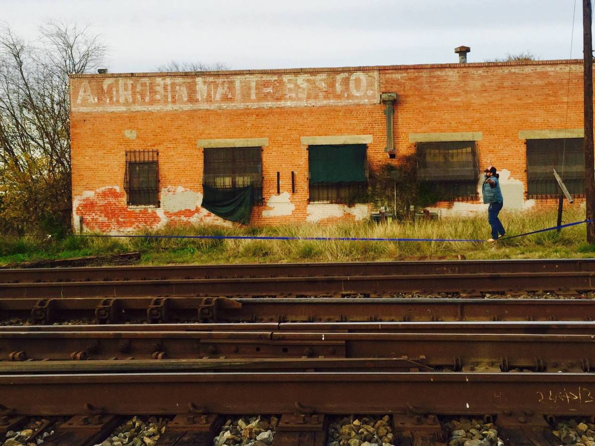 """Skeets Rapier walks a tightrope between the train and the factory. The """"A. Grona Mattress Co."""" sign is still visible and the area is now used to pasture Nigerian Dwarf Goats and chickens."""