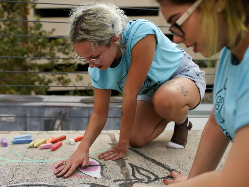 Students from the Henry Ford Academy (Mia, 16, and Miranda, 16) create chalk art on the rooftop of Artpace before the announcement. Photo by Scott Ball.