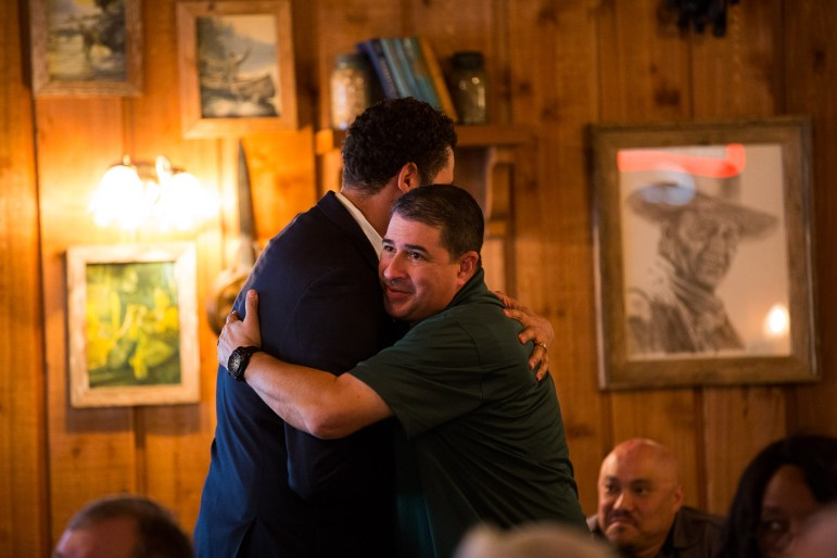 Speaker and fellow Veteran George G. Davila embraces Military and Veteran Affairs Liaison Jon Arnold after his story.
