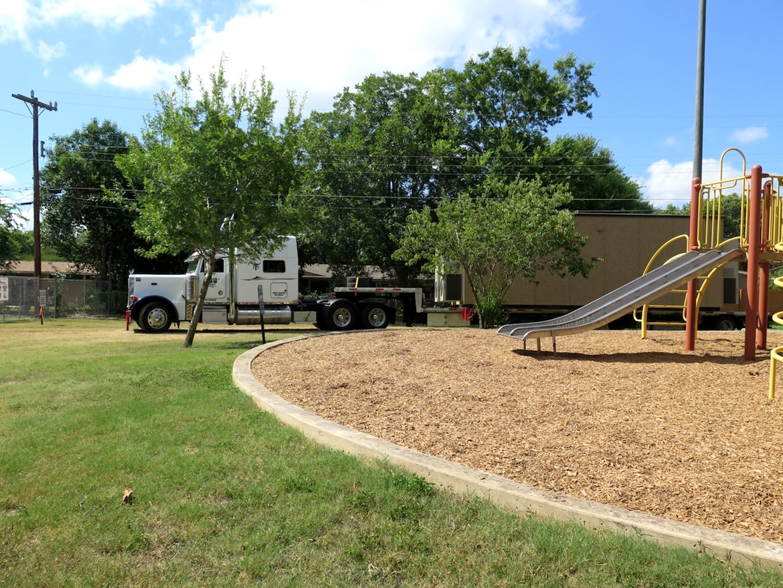 A semi-truck rolls through Haskin Park, carrying a Google Fiber network hut.