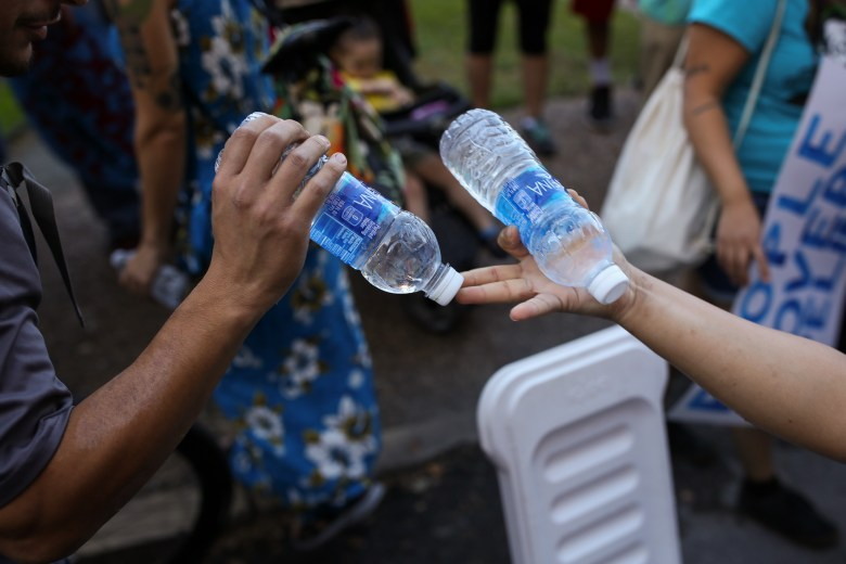 Protestors hand out bottles of water before a march through downtown San Antonio.