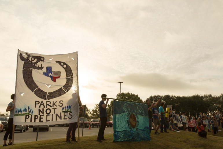 Protestors stand on top of a slight incline overlooking the Texas Parks and Wildlife headquarters.