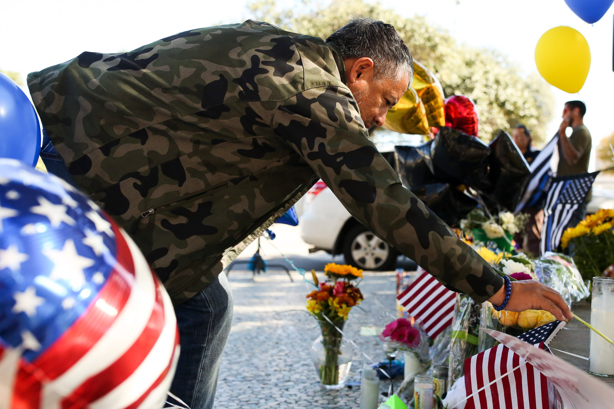 Retired San Antonio Police Officer James Flores places a single flower along with other memorial items in front of the Public Safety Headquarters.