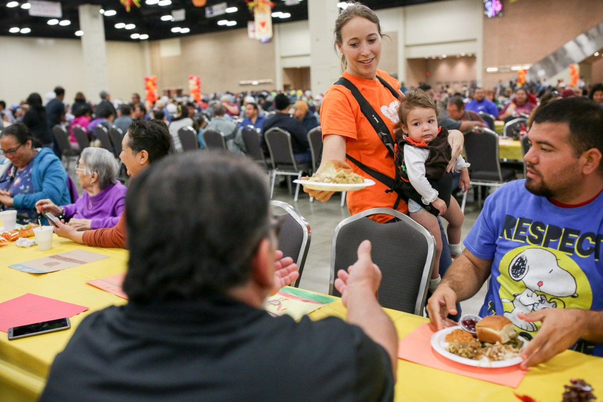 Volunteer Kim Solis serves plates while carrying her 13 month old daughter Lina.