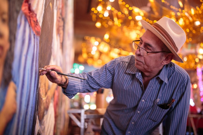 Portraitist and muralist Robert Ytuarte touches up his mural of significant San Antonio leaders.