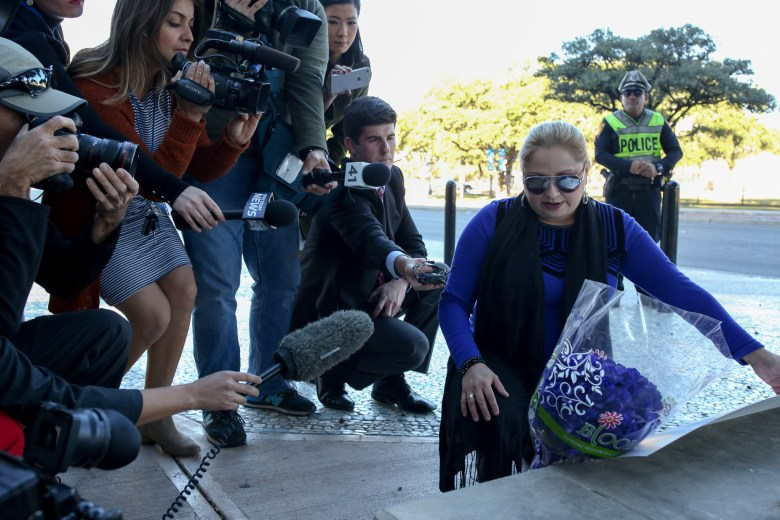 Concerned citizen Lucy Aldaba lays flowers in front of the Public Safety Headquarters.