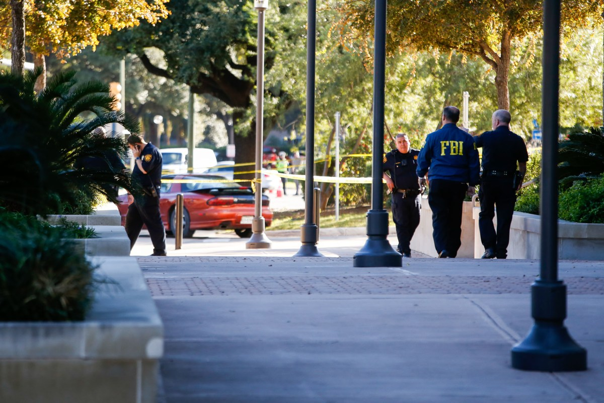 FBI and San Antonio Police Officers make their way to the crime scene just outside of the Public Safety Headquarters in downtown San Antonio.