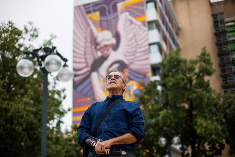 Artist Jesse Treviño stands in front of his nine story tall mural titled Spirit of Healing.