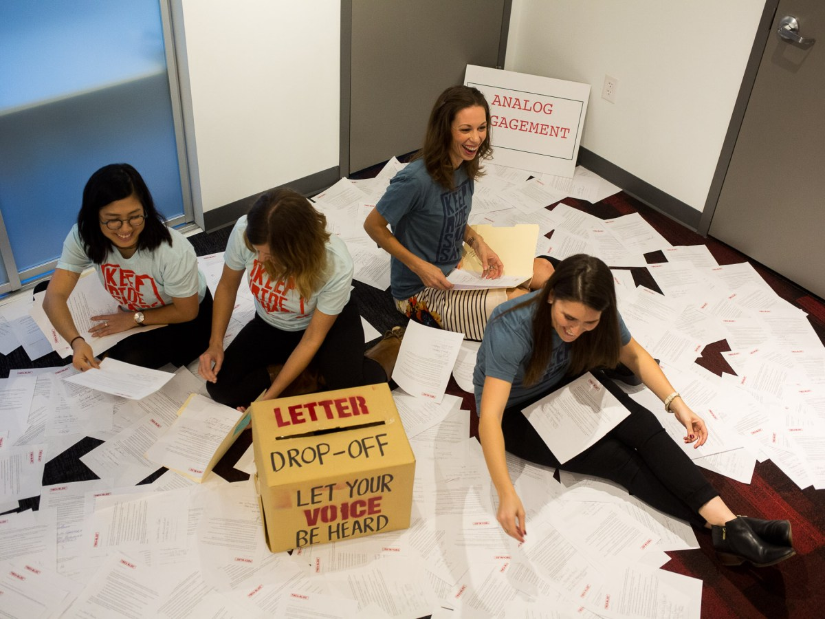 Tech Bloc employees look through the 400 pro-rideshare letters collected at a rally held on Tuesday at Burleson Yard.