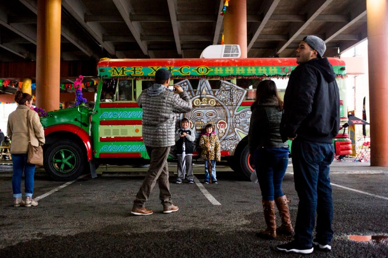 Families take photos in front of a painted bus at the Tamale Festival.