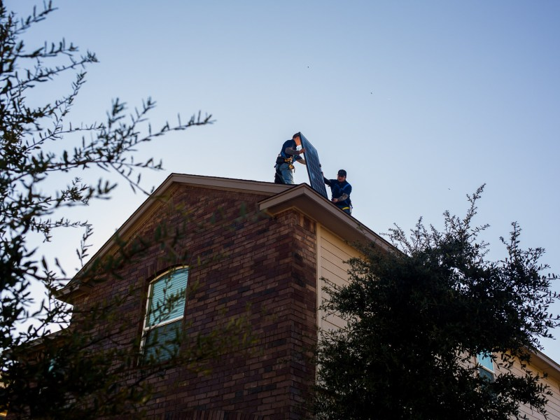 Advanced Solar workers install solar power panels on Peter and Allison Carrazco's roof.