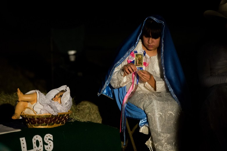 Mary sits with her child, baby Jesus, during the play.