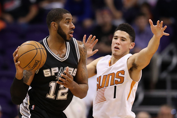 LaMarcus Aldridge #12 of the San Antonio Spurs looks to pass around Devin Booker #1 of the Phoenix Suns during the first half of the NBA game at Talking Stick Resort Arena on December 15, 2016 in Phoenix, Arizona.
