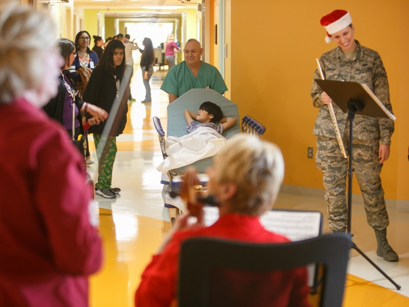 Symphony carolers pause between songs as a patient is transported within the hospital.