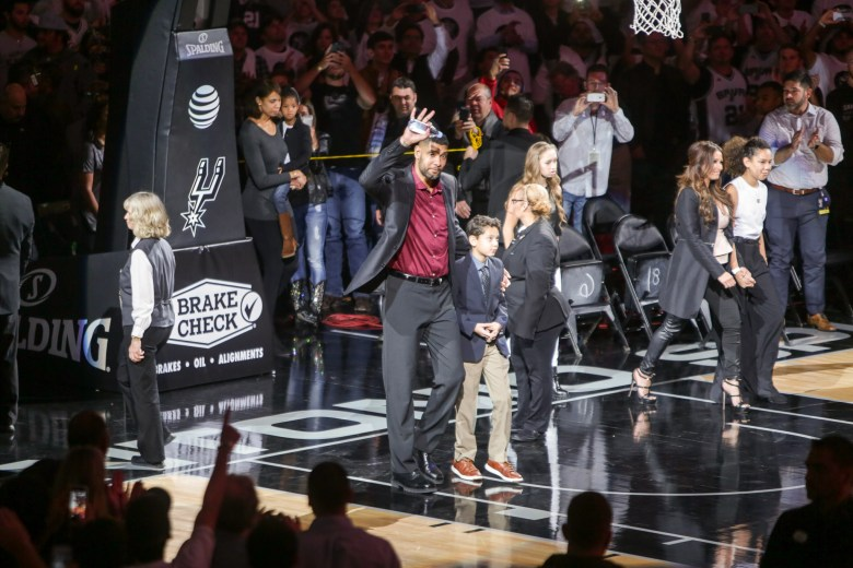 Tim Duncan walks onto the court with his son, Draven Duncan during a standing ovation.