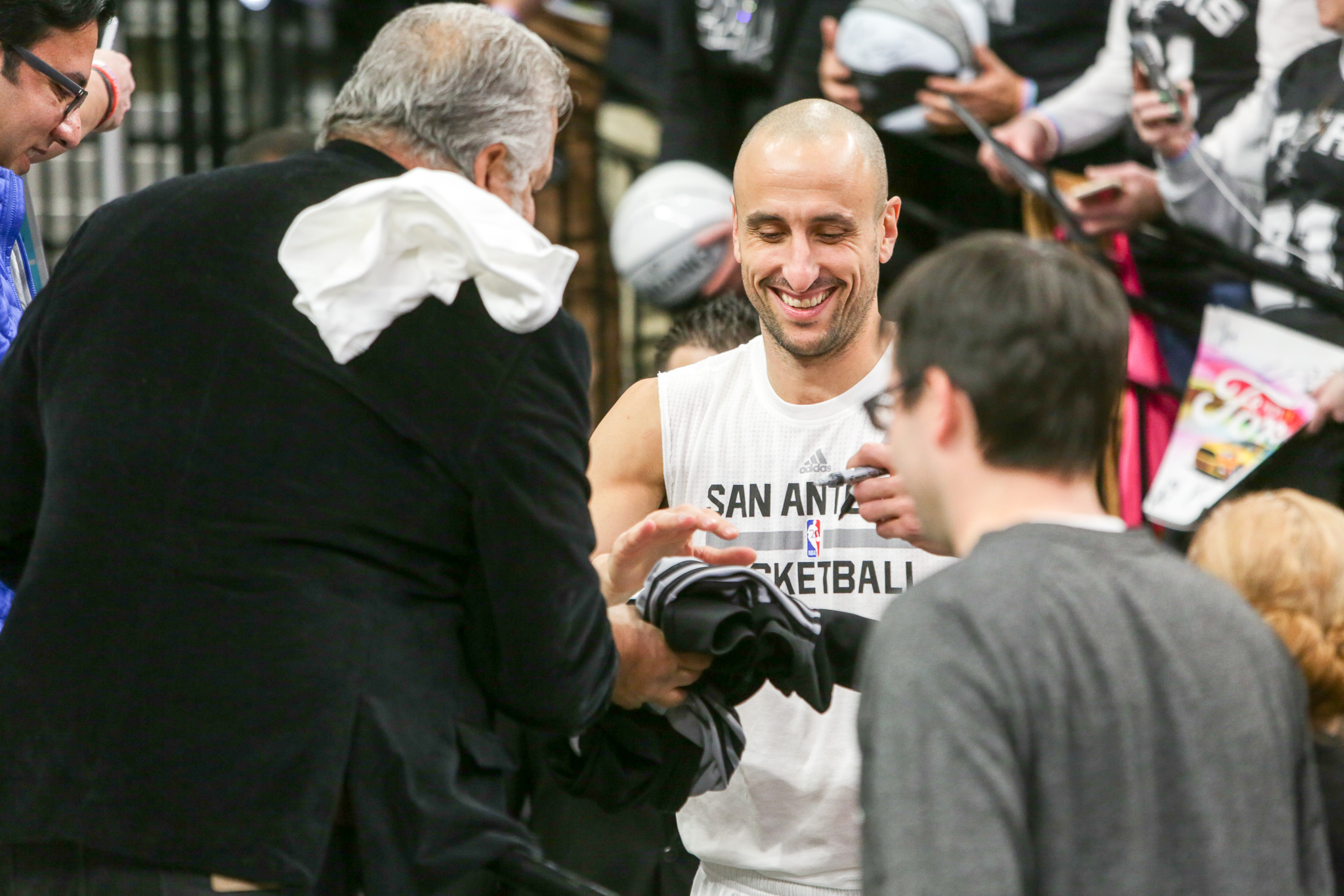 Spurs guard Manu Ginobili signs a jersey for a fan before the game begins.
