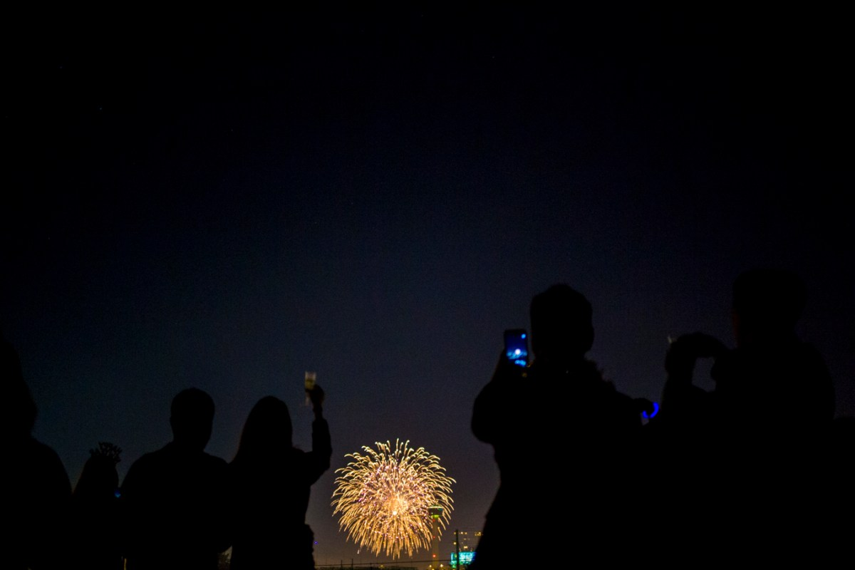 People toast to the new year as fireworks go off near Hemisfair Park in 2017. On Thursday night, the show will move away from downtown and solely to a virtual audience.