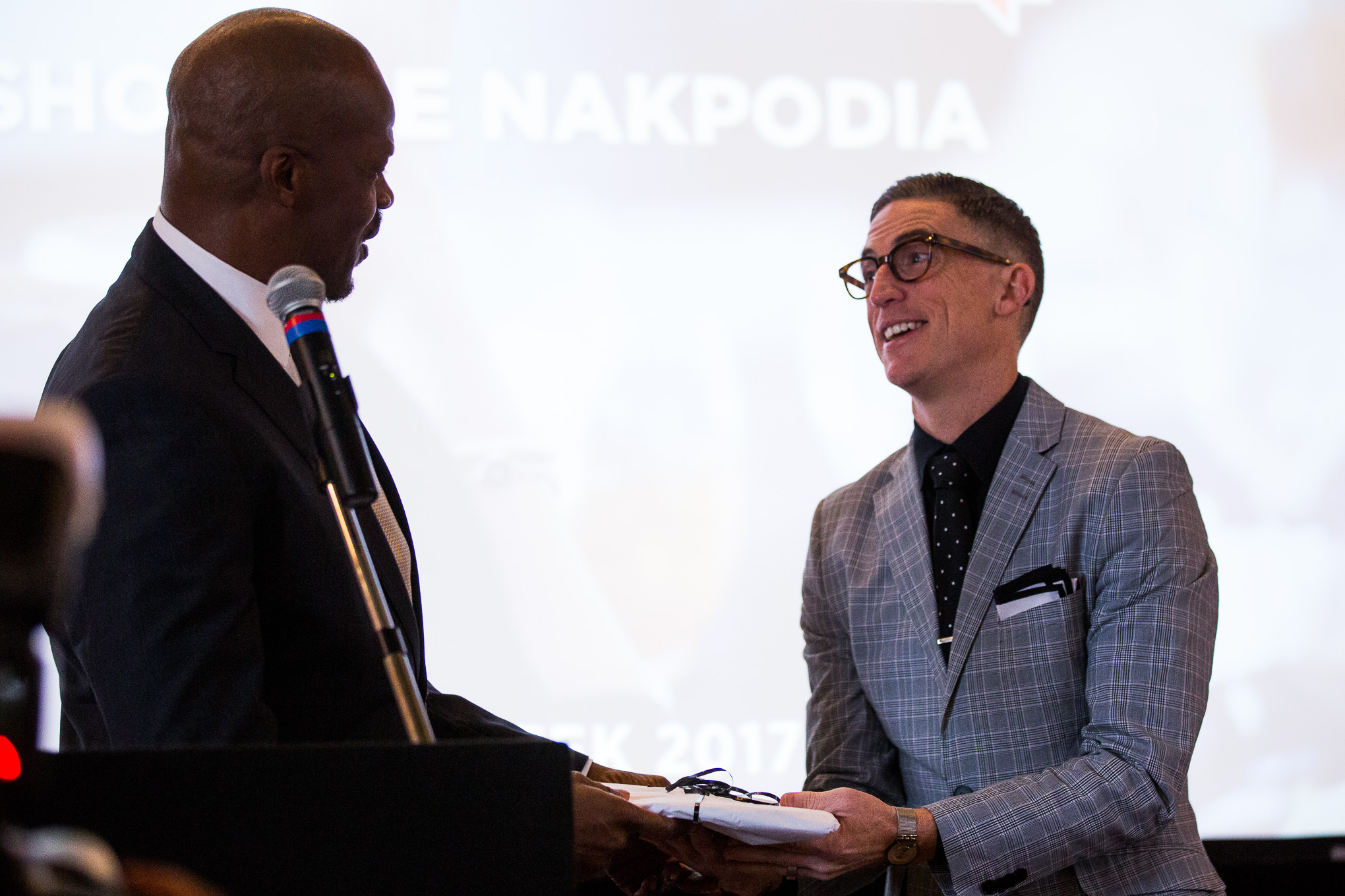 DreamVoice President Shokare Nakpodia gifts keynote speaker Pastor Ed Newton with the photo book 1005 Faces.