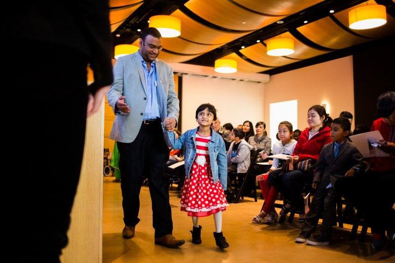 Amarah, age 4 from India, walks up with her dad to accept her U.S. naturalization certificate.