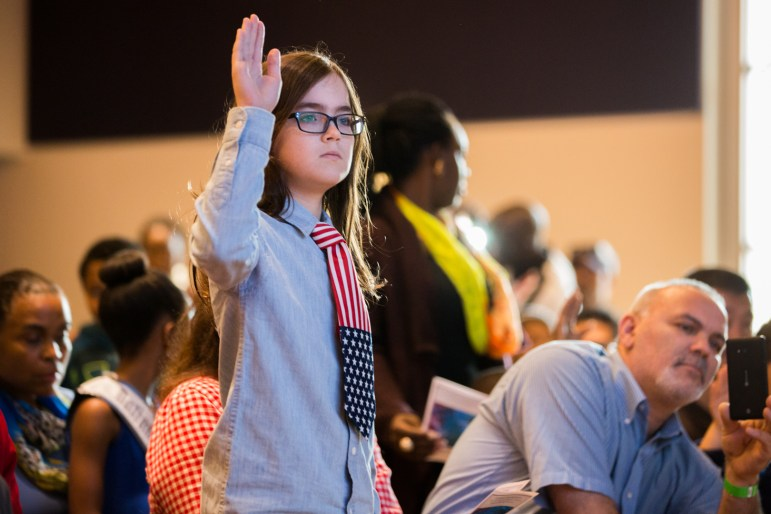 David raises his hand during the Naturalization Oath of Allegiance to the United States of America.