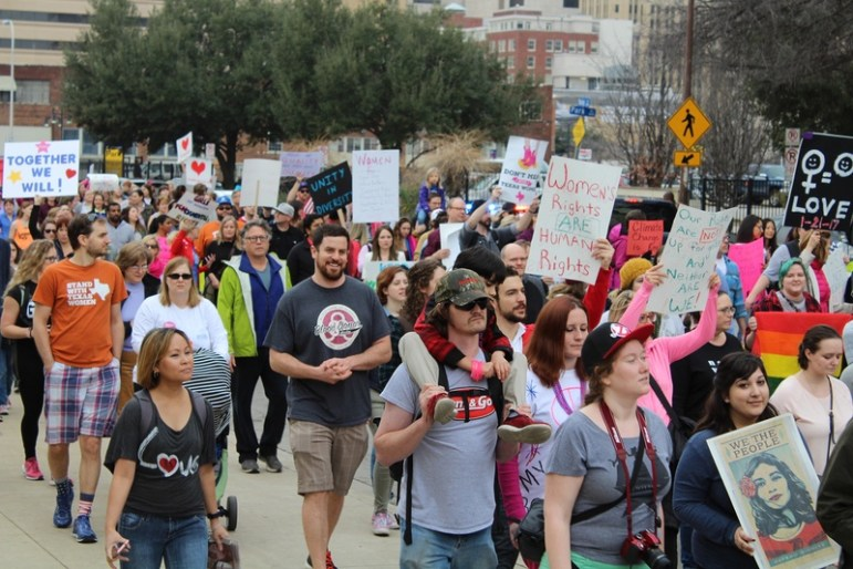 """Thousands of North Texans gathered at Dallas City Hall on the morning of Saturday, Jan. 21, 2017, and began marching through downtown carrying signs and shouting a number of chants, the most common being, """"Women united can never be divided."""""""