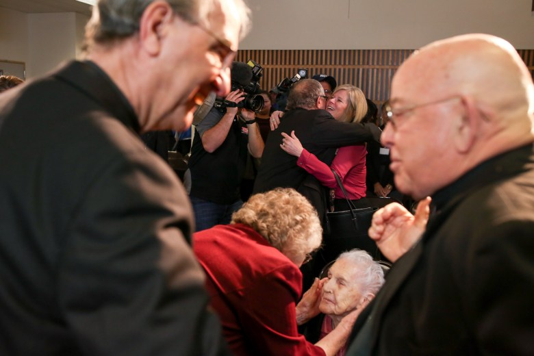 Auxiliary Bishop-elect Michael Joseph Boulette embraces with friends, colleagues, and community members following the announcement along with other members of the Catholic faith.