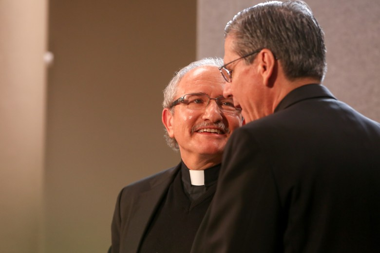 Auxiliary Bishop-elect Michael Joseph Boulette looks on as Archbishop of San Antonio Gustavo García-Siller trade gestures at the podium.
