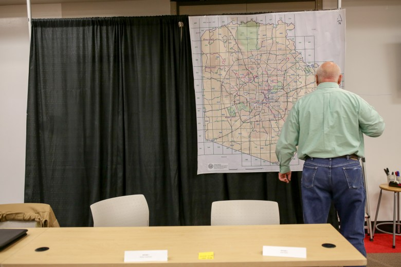 A volunteer looks at a large gridded square map of Bexar County for the annual Point in Time search.