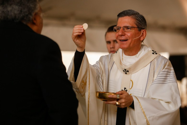 Archbishop Gustavo Garcia-Siller gives the Lord's supper to visitors outside San Fernando Cathedral.