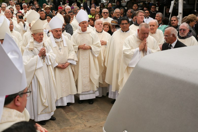 Members of the clergy pay respects to the late Archbishop Flores moments before the hearse drives away.