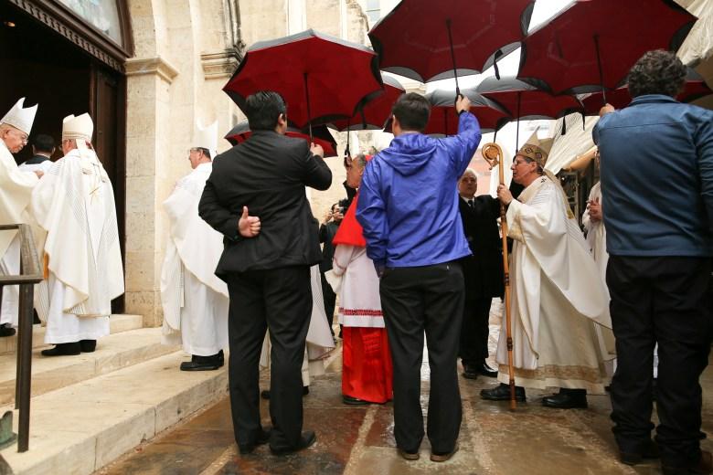 Clergy members along with Cardinal and Archbishop of Houston-Galveston Daniel DiNardo and San Antonio Archbishop Gustavo Garcia-Siller walk under umbrellas upon arrival to the San Fernando Cathedral.