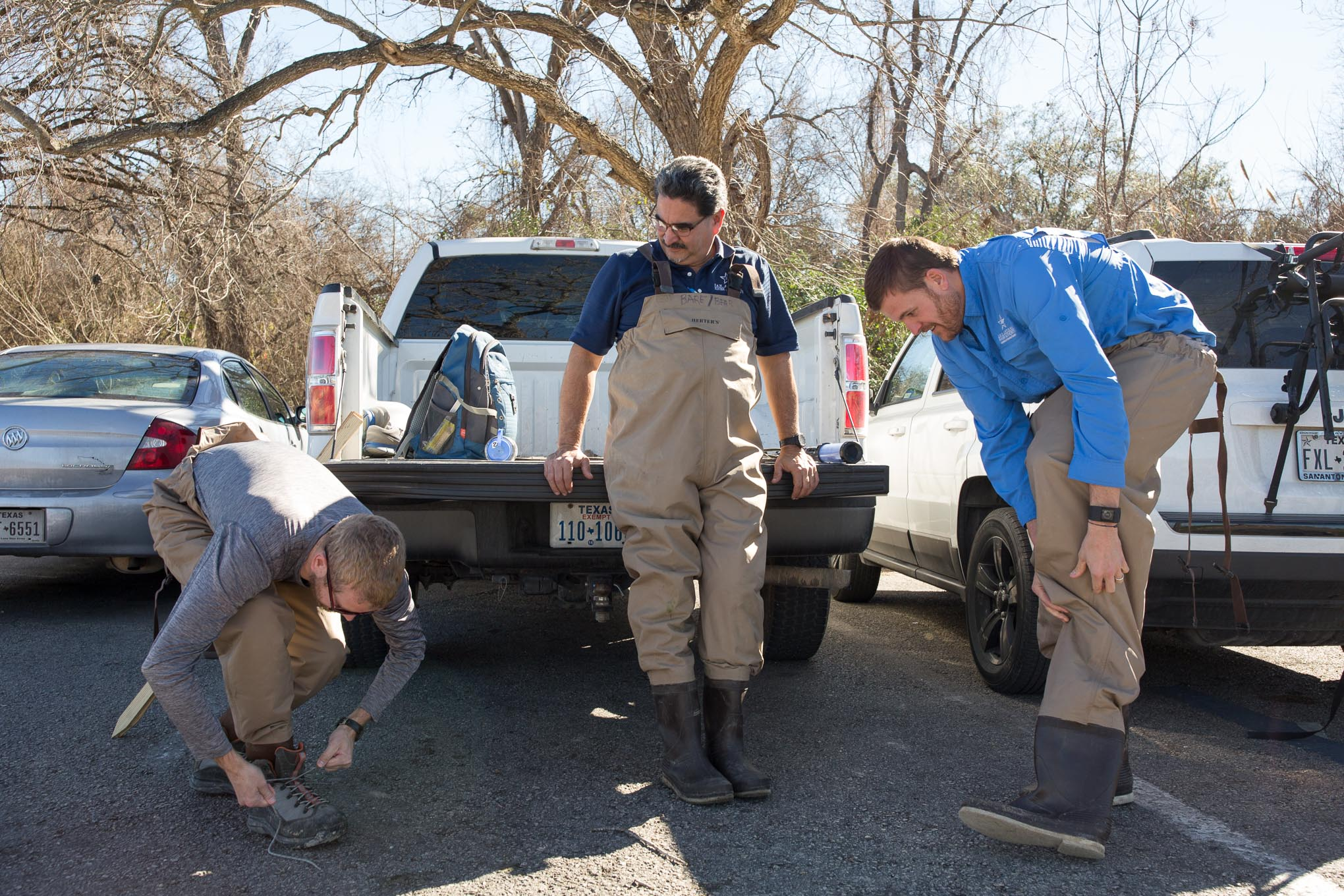 San Antonio River Authority Aquatic Biologists (left to right) Chris Vaughn, Larry Larralde, and Shaun Donovan get dressed into waders before setting out for the San Antonio River.