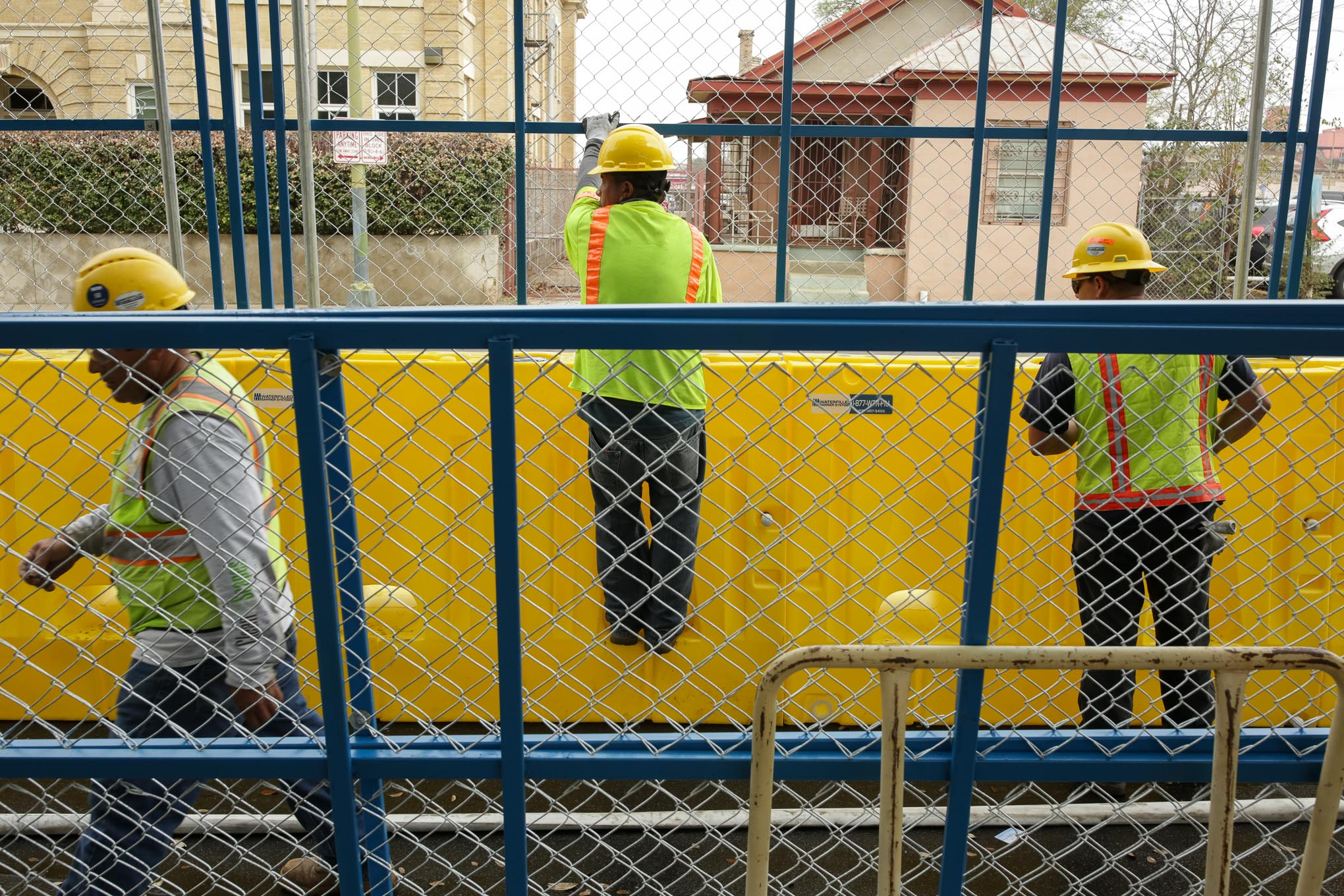 Workers of Waterfilled Barrier Systems assembly a fence and barrier along Travis Street.