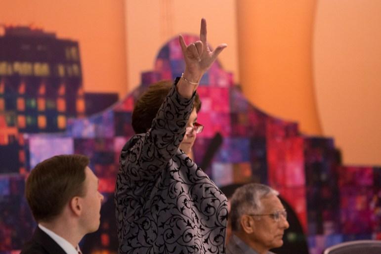 Board Trustee Olga Hernandez (D6) raises her hand following her resignation speech.