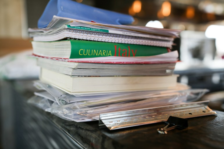 Italian recipes and cookbooks are stacked along the kitchen counters at Battalion.