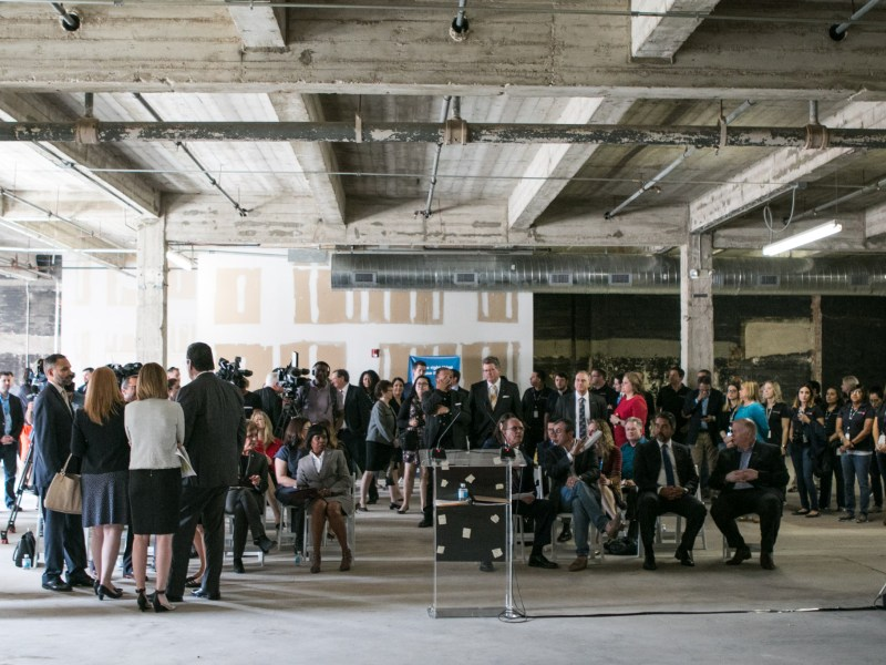 A crowd gathers at a press conference to announce the new CaptureRX corporate headquarters in the Kress building on E. Houston Street.