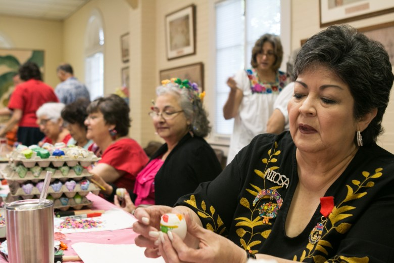 The San Antonio Conservation Society's Cascarones Chairman Maureen Barryman (right) fills an egg with confetti before gluing on tissue paper.