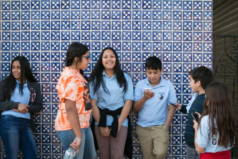 Children and teenagers play on the sidewalk before the Official 21st Anniversary Cesar E. Chavez March For Justice.