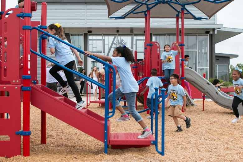 Children from Sinclair Elementary run through the new playground of the Schaefer Branch Library.