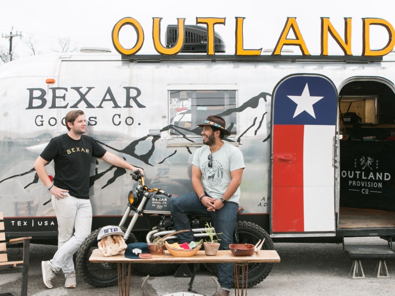 Co-owners of Bexar Goods Company, from left, Falcon Craft-Rubio and Guy Rubio chat outside of the company's streamline trailer retail space located in a parking lot at 2202 Broadway Street.