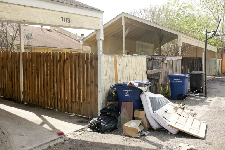 Trash piles up in an alley in Camelot II.