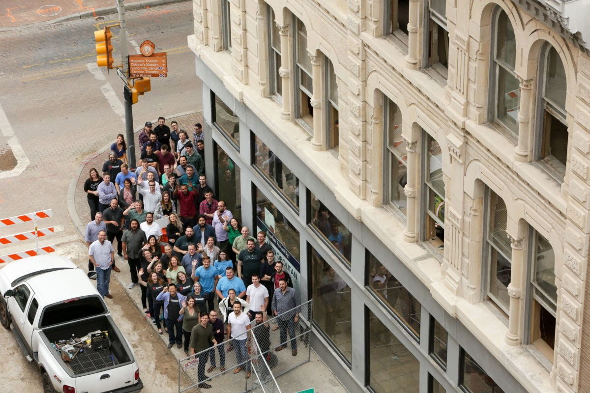 Scaleworks employees stand outside their new office space in the Savoy building.