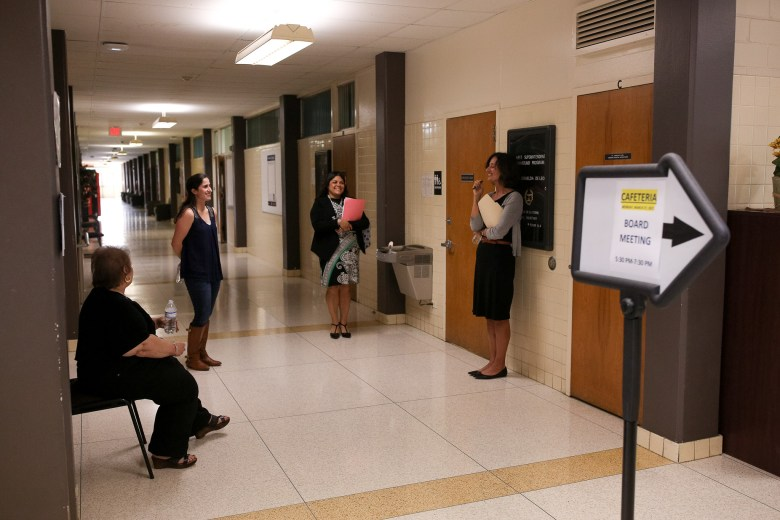District 6 Trustee candidates wait in a hall expecting to hear who should return for a second round of interviews.