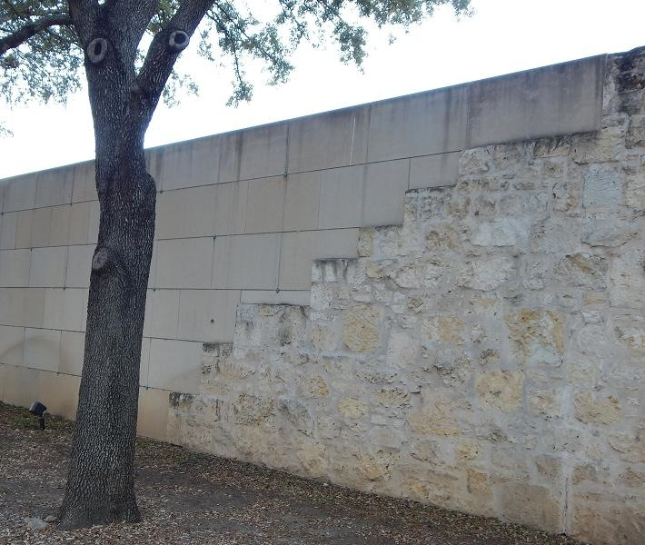 Crisp, modern limestone bricks met with the 19th century limestone on the Frost Motor Bank wall.