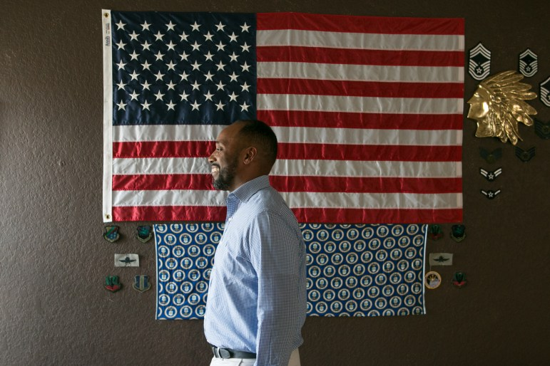 Keith Jordan proudly displays a collection of flags and badges from his days serving in the U.S. Military on the wall of the home he rents out via VRBO.